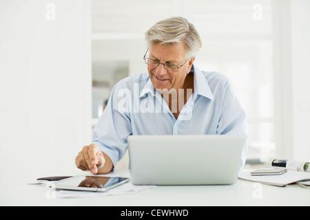 Senior man using digital tablet and laptop computer Banque D'Images