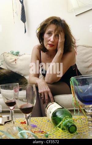 Le port de cheveux brune femme robe noire assis sur le bord du canapé se pencher en avant à la tête de la main à Banque D'Images