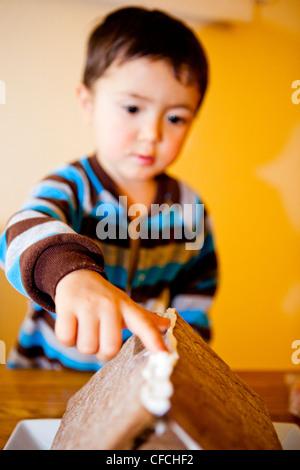Un deux et demi (2,5 ans), fait un pain d'épices maison. Banque D'Images