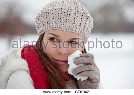 Une jeune femme debout dans la neige, tenant un mouchoir Banque D'Images