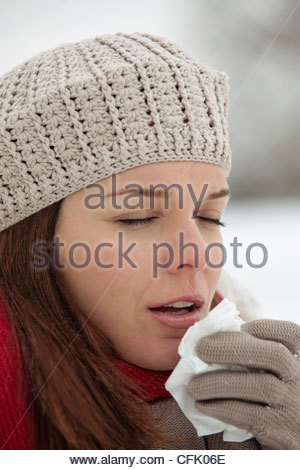 Une jeune femme debout dans la neige, de l'éternuement Banque D'Images