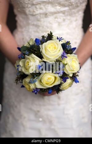 Mariage bouquet de roses crème et fleurs de printemps tenu par une épouse Banque D'Images