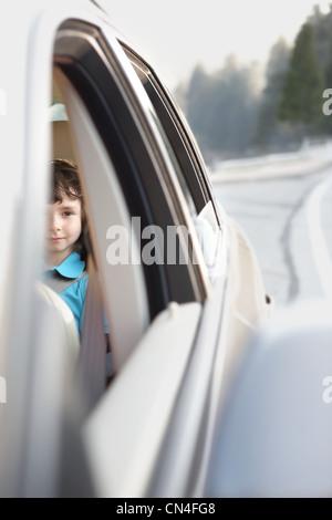 Garçon assis dans le siège arrière d'une voiture Banque D'Images