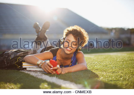 Student listening to mp3 player in grass Banque D'Images