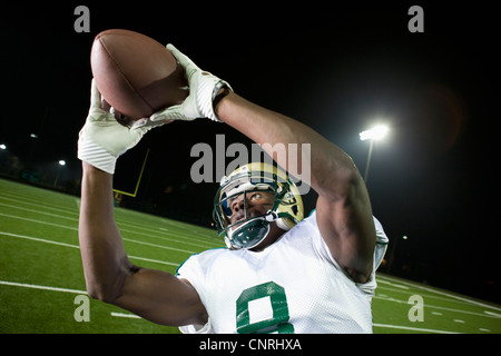 Football player catching ball Banque D'Images
