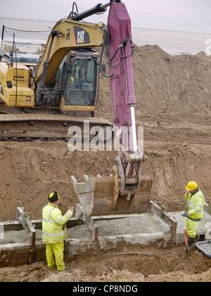 À l'aide d'une excavatrice pour béton prêt à l'emploi dans un faisceau de masse dans la plage d'une nouvelle digue Banque D'Images