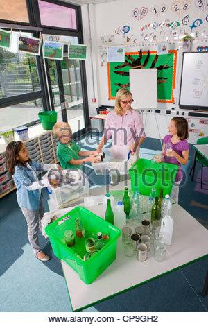 Enseignant et élèves en classe dans les matières recyclables tri Banque D'Images