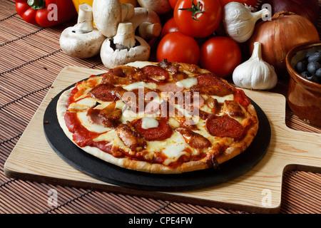 Barbecue Barbecue ou fête de la viande avec une garniture de pizza pepperoni, salami, saucisses et ailes de poulet Banque D'Images