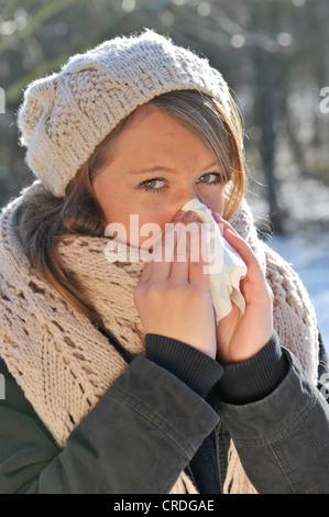 Femme portant un chapeau et un foulard, à l'extérieur, en hiver, s'être mouché le nez Banque D'Images