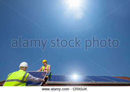 Soleil qui brille plus de ingénieurs installant des panneaux solaires sur toit Banque D'Images