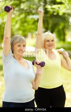 Shot verticale des femmes âgées de faire les exercices avec haltères Banque D'Images