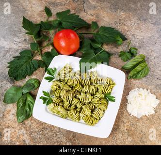 Des Pâtes au Pesto au basilic, persil et tomates sur fond de pierre Banque D'Images