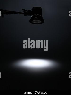 Une lumière photographique de dessus de la création d'un spot blanc sur un fond sombre. Banque D'Images