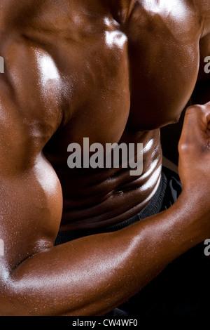 Portrait of a young man flexing muscles dans la salle de sport Banque D'Images