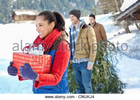 Smiling friends avec de l'arbre de Noël et cadeaux dans la neige Banque D'Images