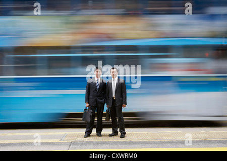 Businessmen standing by blurred bus Banque D'Images