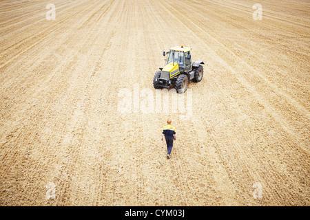 Farmer walking au tracteur dans le champ des cultures Banque D'Images