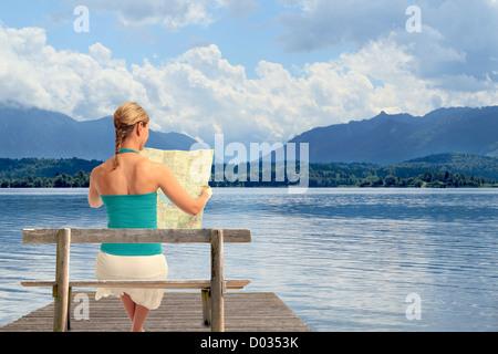 A young woman reading a map assis sur un banc en face d'un lac Banque D'Images