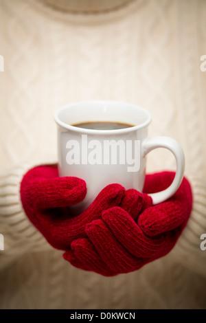 Pull femme avec des mitaines rouges tenant une tasse de café. Banque D'Images