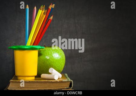 Crayons, craies multicolores et vert pomme sur vieux livre Banque D'Images