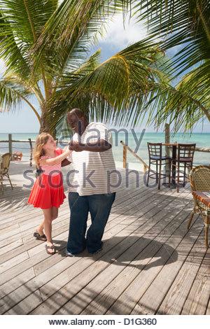 L'homme danse avec un local smiling preteen girl dans les Caraïbes, à Providenciales, Caïques, îles Turques et Caïques, Banque D'Images