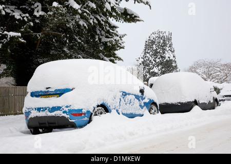 Dormansland, Surrey, Angleterre. Les voitures en stationnement sur la rue couverte de neige épais après blizzard. Banque D'Images