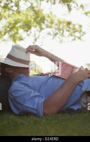 Homme sieste dans l'herbe avec réserve et hat covering face Banque D'Images