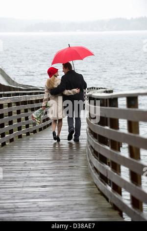 Couple en train de marcher sur la jetée en bois dans la pluie Banque D'Images