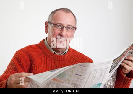 Homme mûr en 50s le port de chandail, la lecture d'un journal grand format, à la caméra à sourire. Banque D'Images