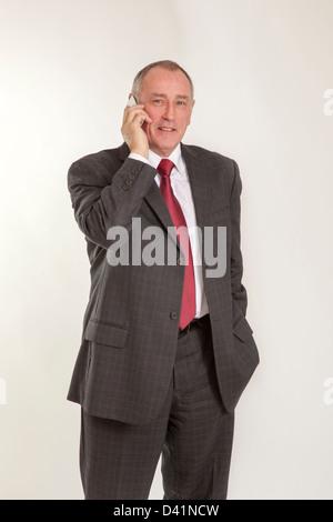Homme mûr en 50s portant un costume gris, l'utilisation d'un cellulaire ou un téléphone mobile, à la recherche à Banque D'Images