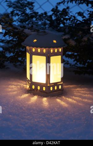 Berlin, Allemagne, une lanterne luit dans la neige fraîchement tombée Banque D'Images