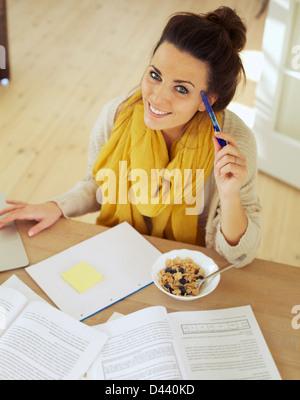 Happy woman holding a pen sitting à la maison à étudier ses livres Banque D'Images