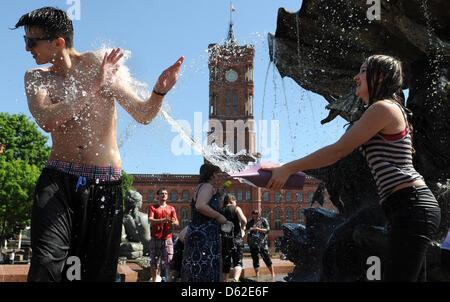 Les jeunes prennent part à une lutte de l'eau à la Fontaine de Neptune, à Berlin, Allemagne, 20 mai 2012. Quelque Banque D'Images