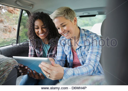 Happy female friends using digital tablet together in véhicule Banque D'Images