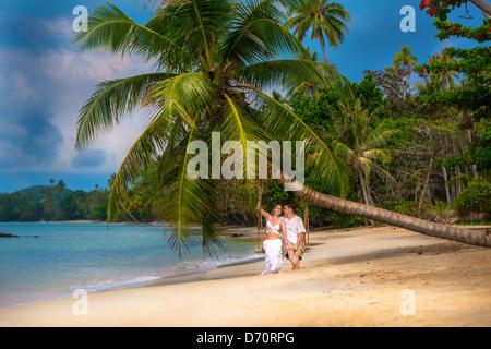 Couple in love sur une balançoire sous un palmier sur la plage Banque D'Images
