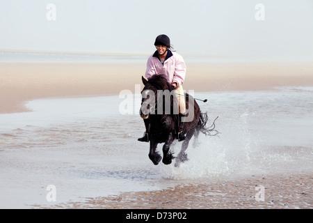 Une jeune femme équitation poney son animal de compagnie sur la plage, Holkham Beach Norfolk, UK Banque D'Images