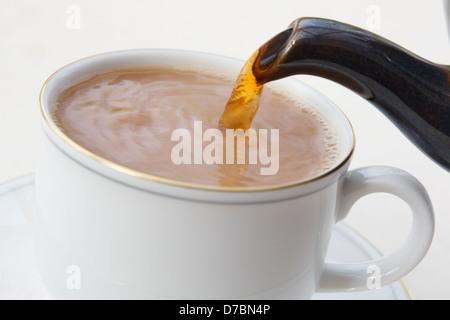 Verser une tasse de thé anglais britannique de la tuyère d'une théière dans une tasse de lait avec la Chine blanc Banque D'Images