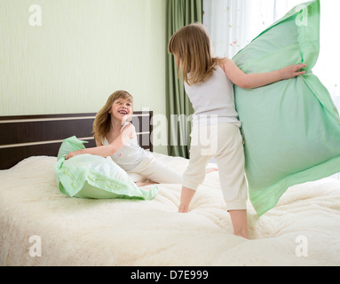 Deux jeunes filles jouant avec des oreillers dans la chambre Banque D'Images