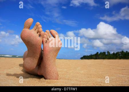 Pieds de sable sur une plage tropicale Banque D'Images