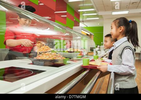 Les enfants de l'école dans la file à l'école cafétéria Banque D'Images