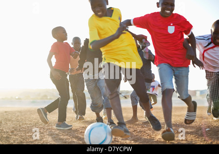 Boys playing soccer together in dirt field Banque D'Images