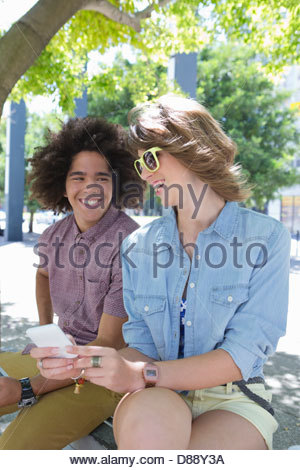 Smiling young couple text messaging with cell phone in urban park Banque D'Images
