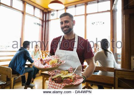 Portrait of male deli owner holding food in restaurant Banque D'Images