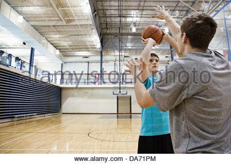 Les hommes jouant au basket-ball en salle de sport Banque D'Images