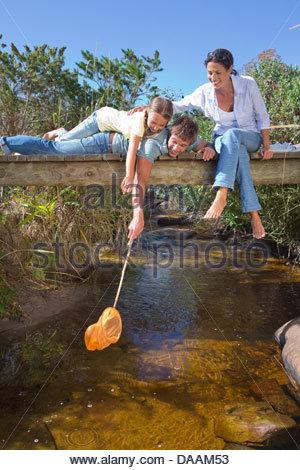 Pose de la famille sur la passerelle et trempant dans le flux net de la pêche Banque D'Images
