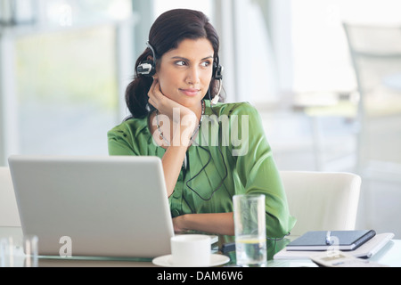 Businesswoman wearing headphones at desk Banque D'Images