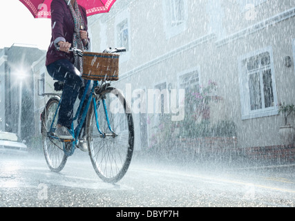 Woman riding bicycle with umbrella in rainy street Banque D'Images