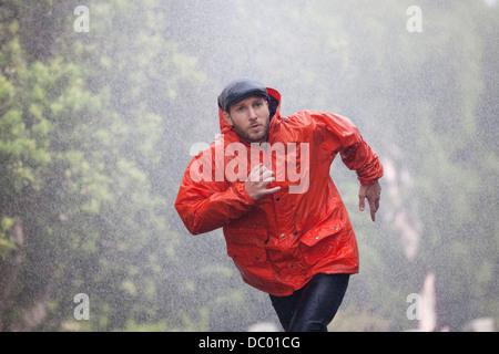 L'homme à l'imperméable en marche dans la pluie Banque D'Images