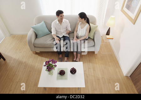 Couple chatting in living room Banque D'Images