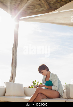 Woman using digital tablet on sunny patio Banque D'Images